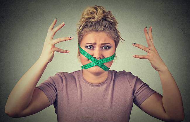 frustrated-woman-with-measuring-tape-around-mouth