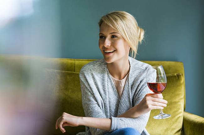 happy-woman-holding-glass-of-red-wine-on-sofa