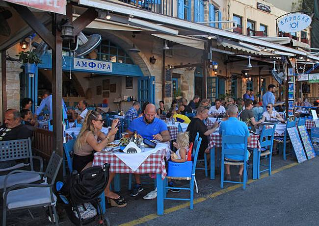 people-sit-in-sidewalk-street-cafe-in-chania-waterfront-crete
