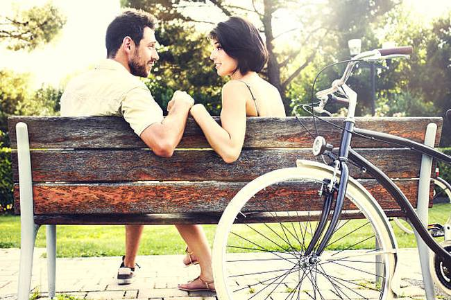 couple-in-love-sitting-together-on-a-bench-with-bikes