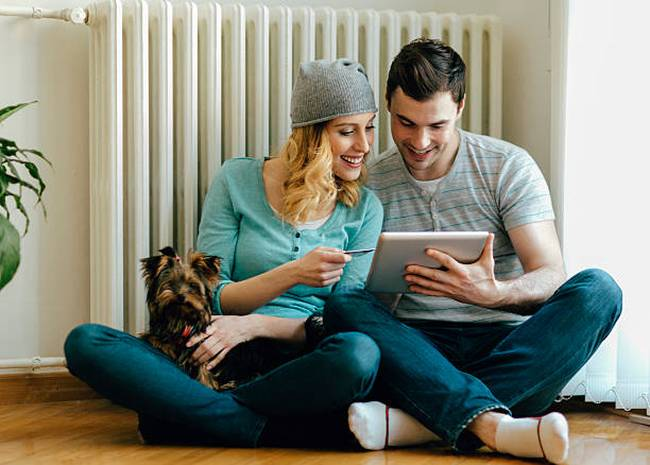 couple looking at an ipad with radiator at the background