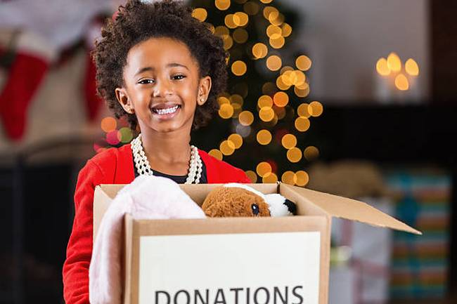 african-american-child-holding-box-of-toy-donations-at-christmastime