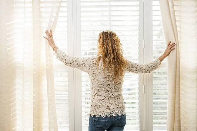 woman-looking-out-of-window-blinds